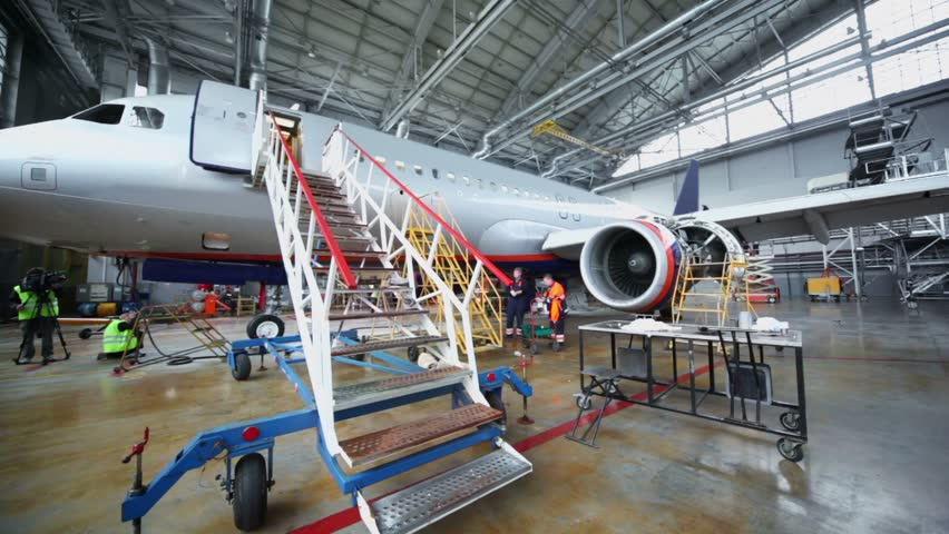 People work near aircraft under repair in hangar with staircase