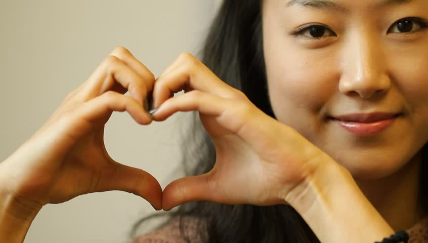 Beautiful young Asian woman making love heart gesture with hands
