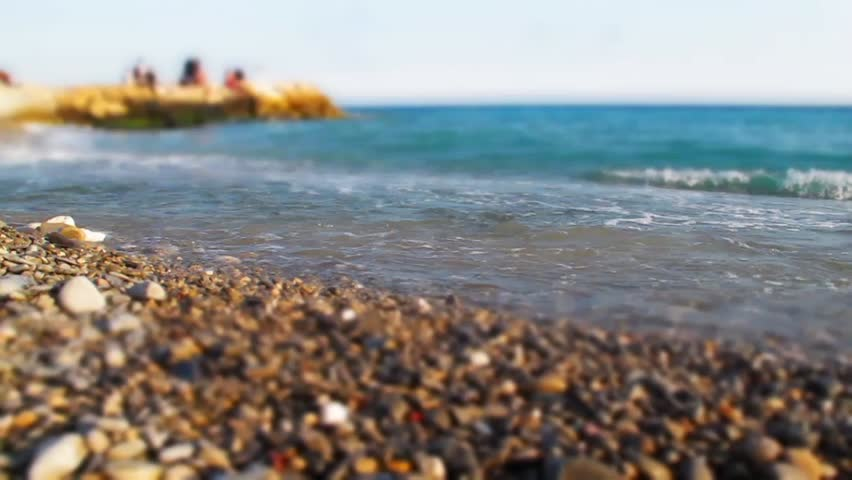 Focus on coastline, pebble and waves of blue sea in motion. Sandy beach, people in background. Tranquil seascape. Beautiful view with scenic landscape. Idea of summer vacations. Relax on beach.