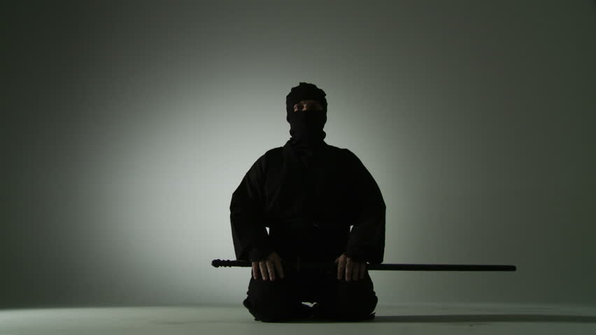 Low angle view of a masked ninja unsheathing a short sword, holding it and then re-sheathing it while kneeling on the floor.