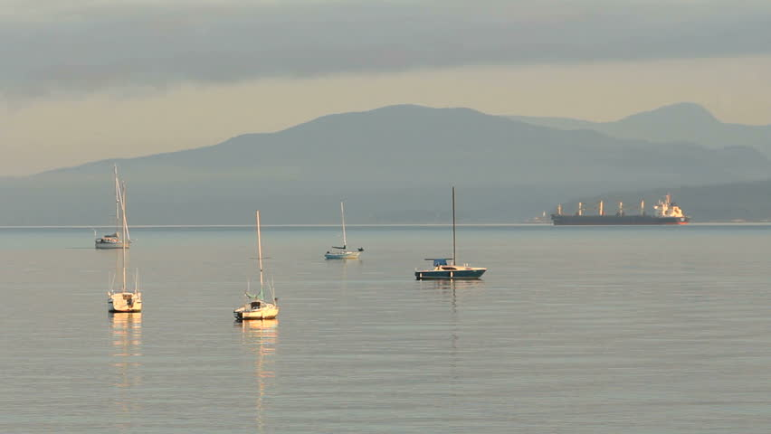 Sailboat Motoring at Dawn, Vancouver. A sailboat motors past anchored sailboats at dawn in English Bay, Vancouver, British Columbia, Canada.