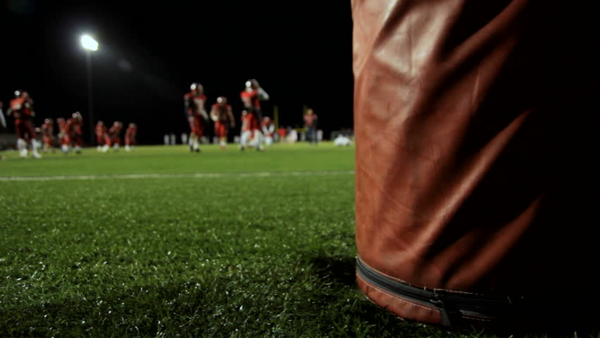 Dolly behind a goalpost as football players warm up before a night time game.
