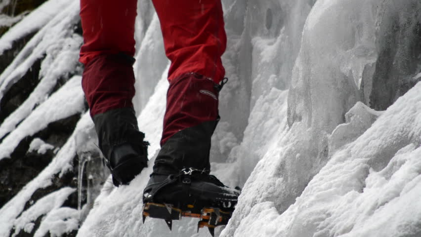 ice climber in background climbing frozen waterfall and crampon closeups