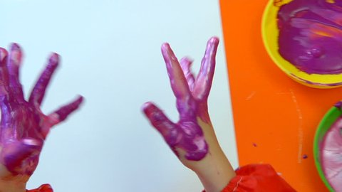 Overhead shot of a child making handprints with paint