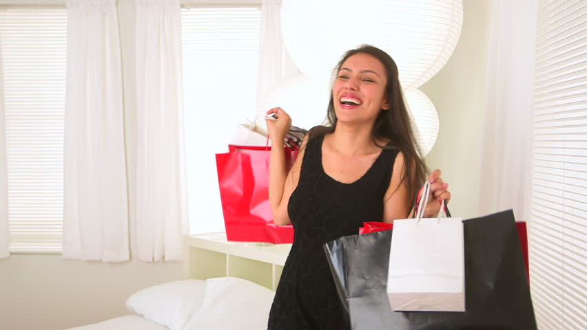 Happy Young Hispanic woman with shopping bags spinning around