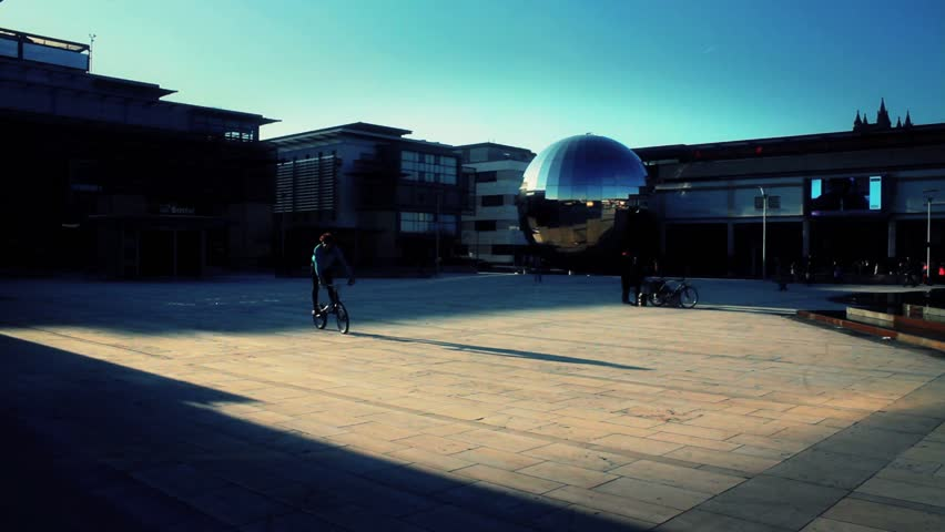 BRISTOL - April 6: Cyclist Passes Through Millennium Square & Does Trick on BMX Bike on April 6, 2013 in Bristol, England.