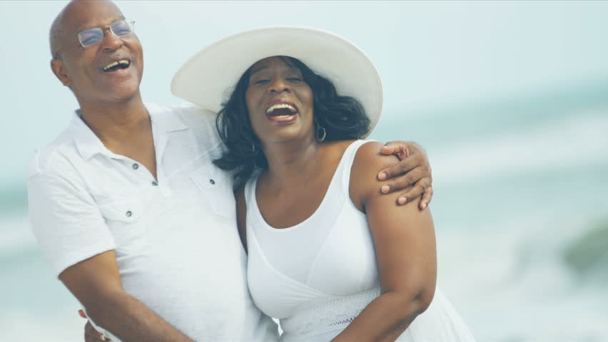 Laughing senior ethnic couple enjoying quiet time together in shallows on beach shot on RED EPIC