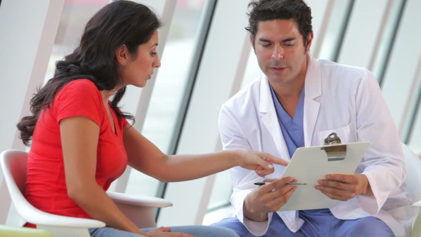 Doctor discusses female patients notes on clipboard. Shot on Canon 5d Mk2 with a frame rate of 30fps