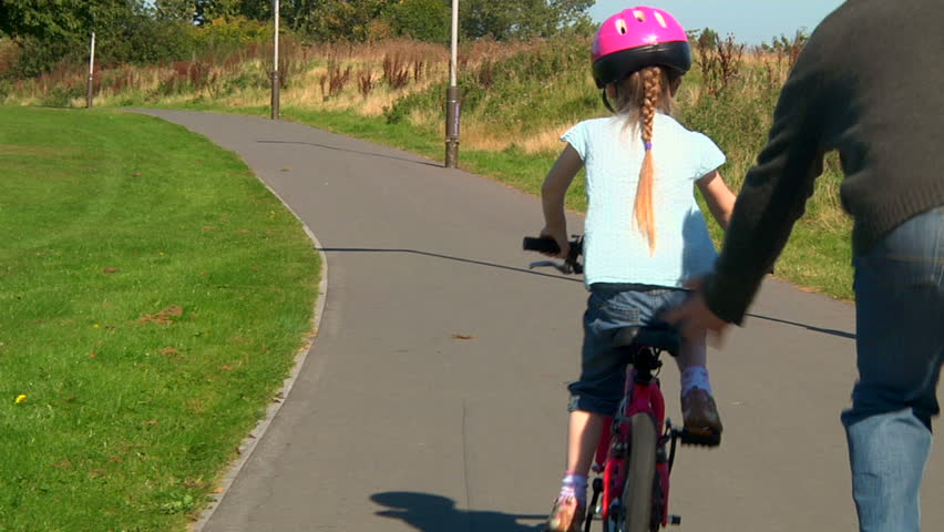 Little girl learning to ride her bicycle with help from her dad - dolly