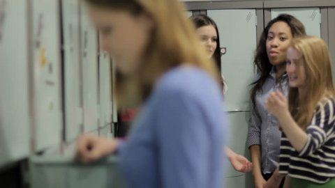 Bullying - a multi ethnic group of girls bully another girl, in a school locker room