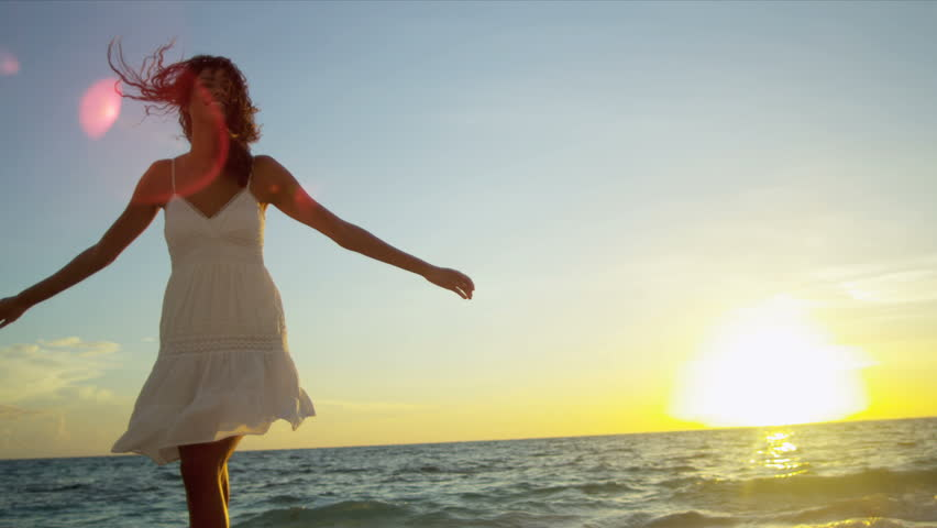 Pretty girl in sundress reveling being alone by ocean at sunrise on beach vacation shot on RED EPIC