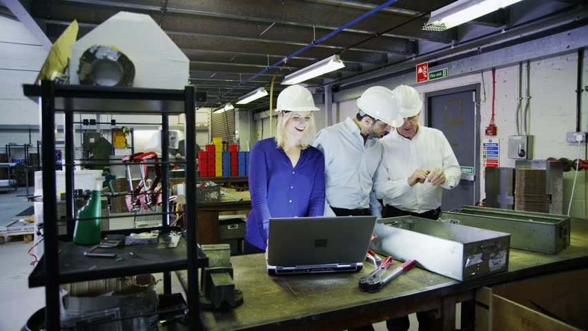 Male and female warehouse managers are looking at a laptop computer and discussing the logistics of their business.