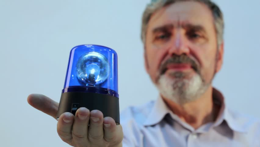 Aged man with beard holds blue flasher on hand, focus on blinker
