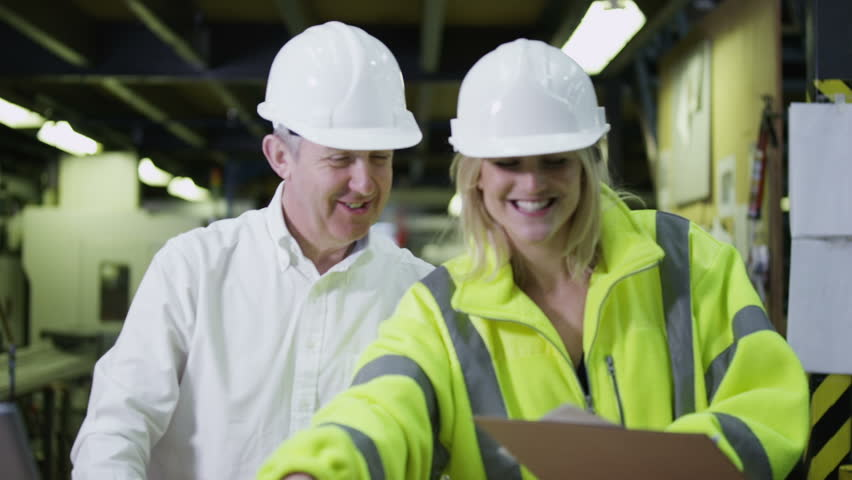 A happy team of workers in a warehouse or factory are going about their business and preparing goods for delivery. One male staff member is checking the inventory on a laptop computer. In slow motion.