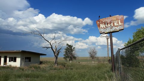Timelapse of clouds behind an old, creepy, abandoned motel in rural Colorado, complete with bullet-holes in Motel sign, old tree, and gutted building.  HD 1080p Time lapse.