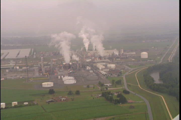 CONVENT, LOUISIANA - CIRCA SEPTEMBER 1999: Aerial shot of oil tanks and smoke spewing from oil refineries and chemical plants in Convent, LA.