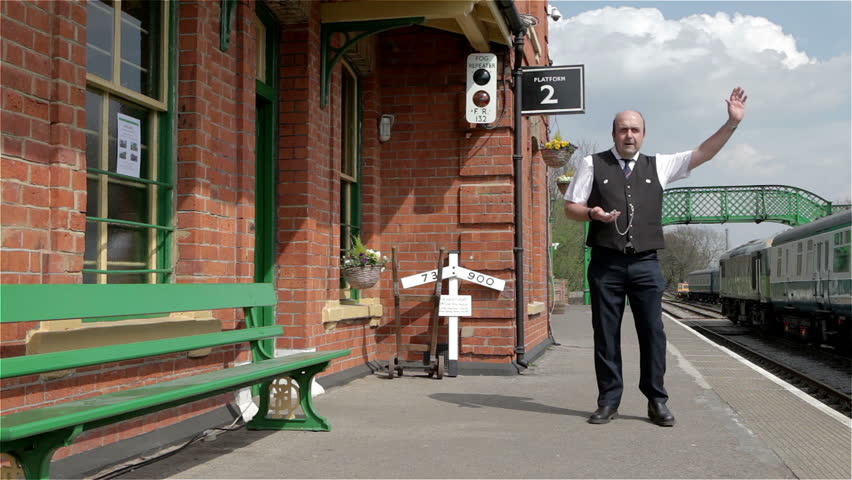 British Railways: a quaint rural British train station with a station master checking his watch on the platform.