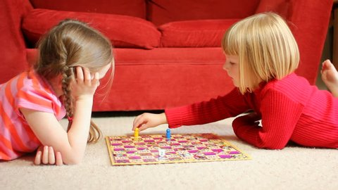 Two little girls playing a board game - lying on the floor