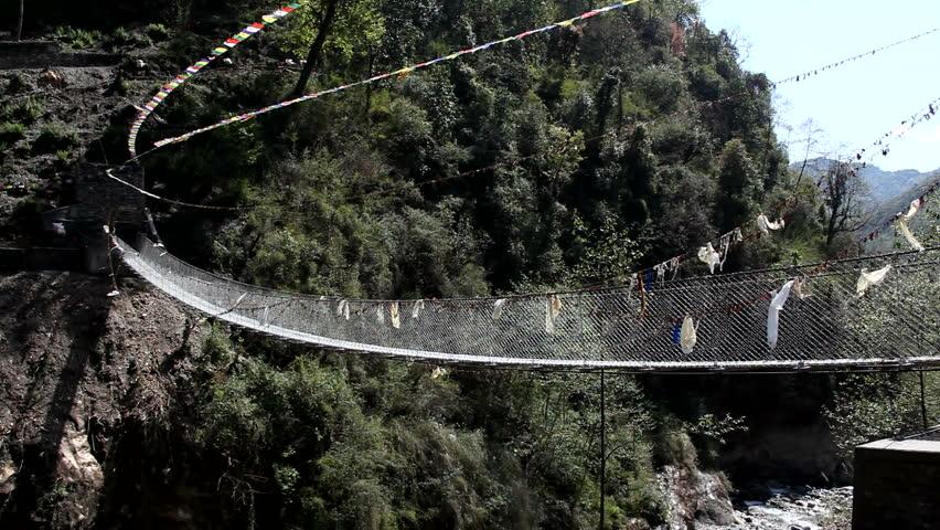 River Bridge In Rural Nepal Buddhist Prayer Flags. Gurkha built bridge in rural