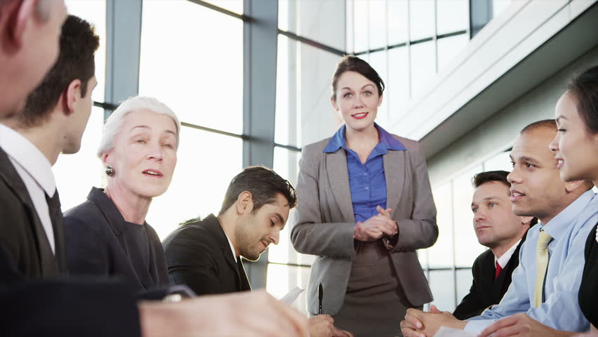 A confident and happy business team of mixed ages and ethnicity are holding a meeting in a light, modern office building. They applaud a comment from one of the group  | Shutterstock HD Video #3847940