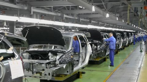 TOGLIATTI - SEP 30: Workers assemble cars Lada Kalina on conveyer of factory VAZ on September 30, 2011 in Togliatti, Russia. AvtoVAZ factory was founded in 1966