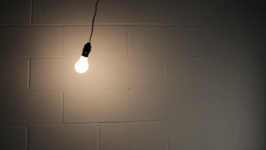Light In Dark Room abstract swinging light bulb in dark room stock footage video