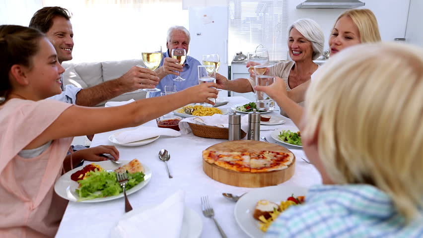 Family toasting at dinner table at home in kitchen | Shutterstock HD Video #3870227