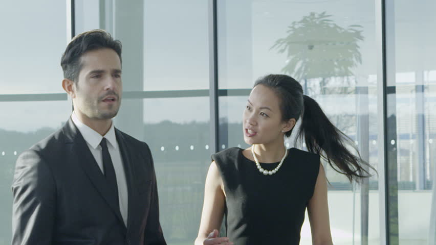 An attractive mixed ethnicity businessman and businesswoman chat together as they walk around their light and modern office building. In slow motion.