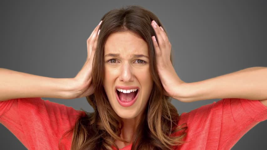 Frustrated woman holding her head between hands on grey background in slow motion