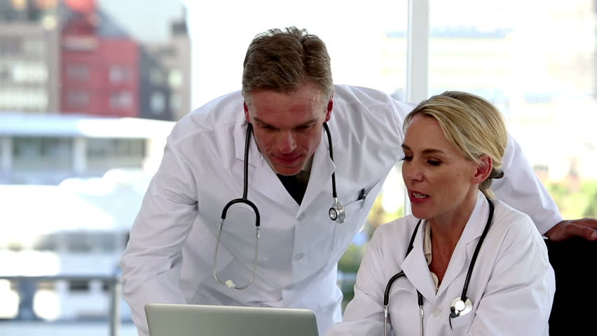 Team of doctors working on a computer while someone is bringing a folder
