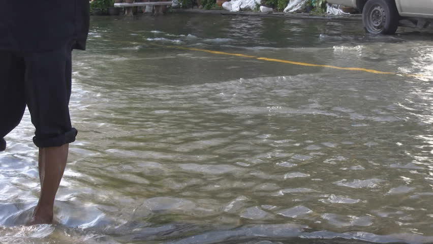 Bangkok, Thailand - October 2011: A bottle floats down a flooded road and is picked up by a barefooted man with his trousers rolled up.