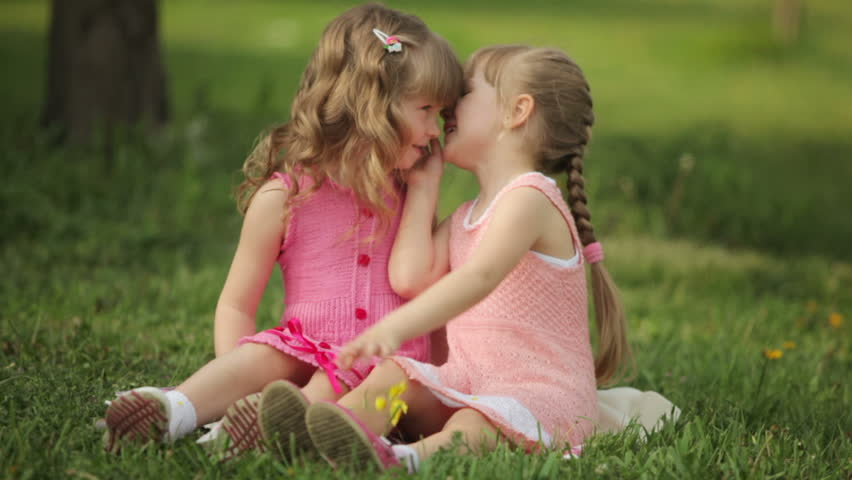 Two girls sitting on the grass and laughing