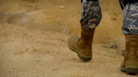 Ungraded shot of Army soldier walking up a road legs only