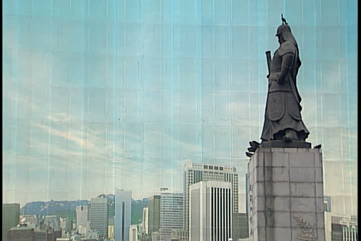 SEOUL - FEBRUARY 26, 1997: MS statue of Admiral Yi Sun Sin reflected on side of glass building. WS showing statue, building, and traffic passing on Sejong Avenue.