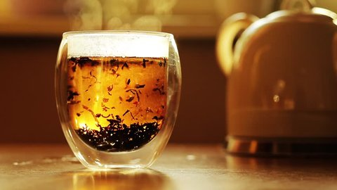 Brew black tea in a beautiful glass bowl, back light, brown color