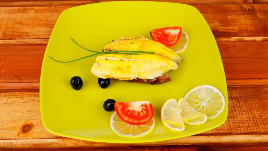grilled fish fillet served over wood with tomatoes olives and bread 1920x1080 intro motion slow hidef hd