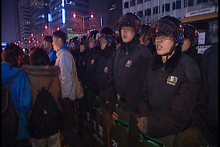 SEOUL - MARCH 02, 2003: Night time peaceful anti-war demonstration in Jung-gu; MS line of riot police in helmets standing by, along side of crowd. | Shutterstock HD Video #3933971