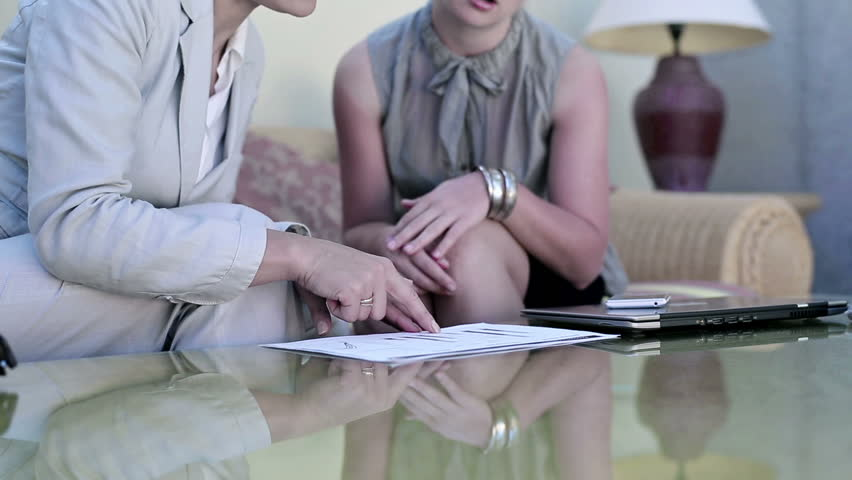 Two young businesswoman sitting in hotel lounge with laptop and documents    Shutterstock HD Video #3947105