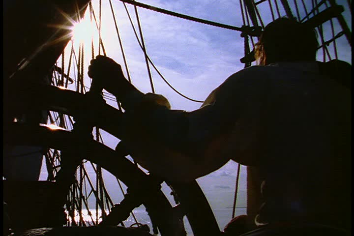 Historical reenactment of HMS Bounty ship on Rhode Island. MS silhouette of crew member with hand on ship's wheel. Rigging, open sea, clouds and blue sky in background.