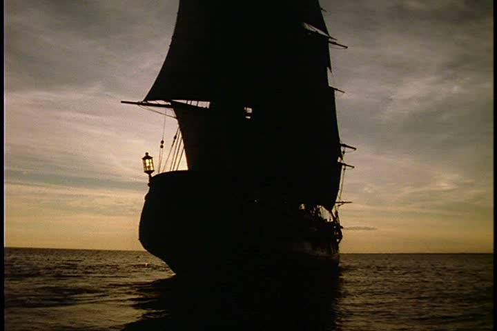 Historical reenactment of HMS Bounty ship on Rhode Island. MS silhouette of HMS Bounty from the back as it heads into the sun. Sun is very bright and low in the sky.