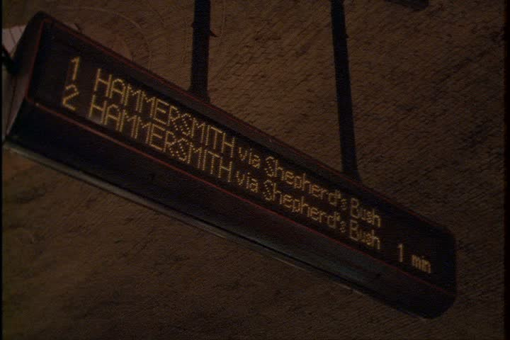 LONDON - AUGUST 09, 1999: Interior shot of London Underground Baker Street tube station; MS electronic sign showing arrival time for Hammersmith train, MS train leaving the station.  #3975877