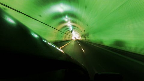 Wide angled, moving vehicle shot driving through tunnel in downtown Los Angeles California at night. Edited in fast motion and really captures the rapidly changing colorful lights along the tunnel.