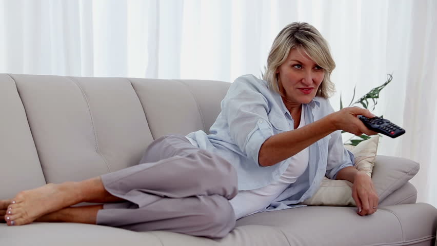 Blonde woman lying on her sofa watching television and relaxing