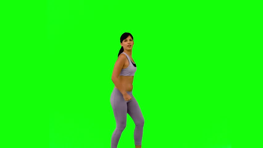 Athletic woman jumping and posing on green screen in slow motion | Shutterstock HD Video #3996880
