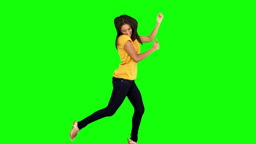 Cheerful woman jumping with legs and arms raised on green screen in slow motion #3997447