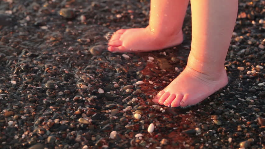 Cute little girl stands on the beach (close-up of feet)