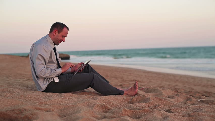 Businessman working on tablet computer on the beach