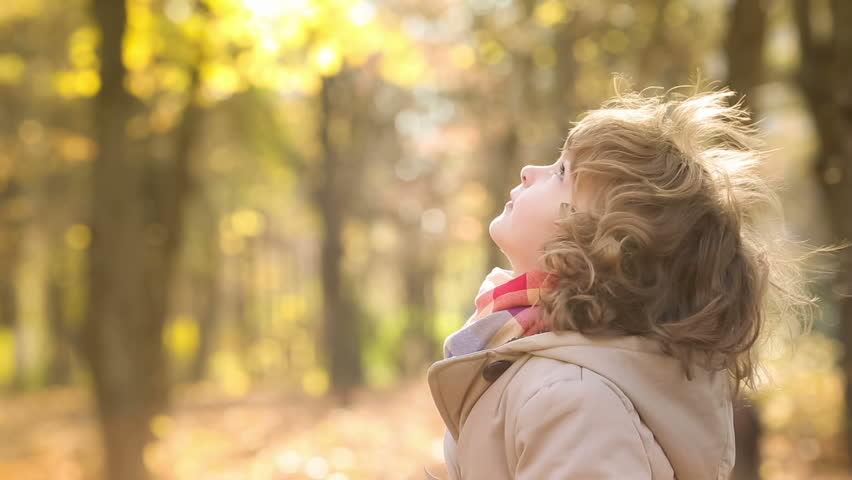 Happy child playing outdoors in autumn park