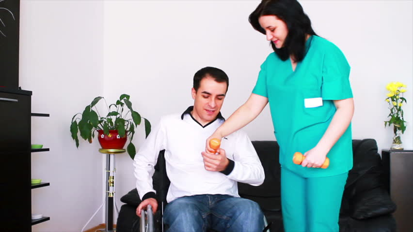 Therapist assists patient with weight lifting. Young adult in wheelchair.