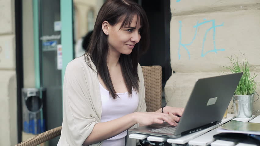 Young woman working on laptop in cafe, steadicam shot
